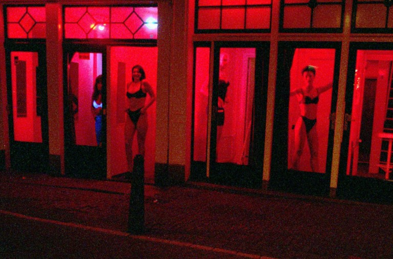 """FILE-Prostitutes stand behind red-lit windows, waiting for customers in Amsterdam's Red Light district in this September 28, 1997 file photo. With its scantily-clad prostitutes posing in brothel windows and coffee shops oozing the pungent aroma of cannabis smoke, Amsterdam's Red Light District has always thrived on its illicit atmosphere. But while the city has long tolerated coffee shops where marijuana is sold openly and fully legalized prostitution, authorities say the network of cobbled alleys and canals is a haven for organized crime where mobsters launder money through real estate, brothels and bars. """"We are very worried about the mixing of the underworld with the above board in the center of Amsterdam,"""" the city said Thursday in a press release. """"Particularly in the Red Light District, money laundering from real estate... and involvement of organized crime in prostitution, coffee shops, smart shops, and parts of the hotel industry is a cause for concern."""" The problem is well-known, but few dare to file complaints and evidence is difficult to gather, the statement said. (AP Photo/Peter Dejong)"""