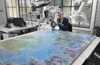 Gemeentemuseum restorer Ruth Hoppe examines Monet's Wisteria painting. Image courtesy Gemeentemuseum.